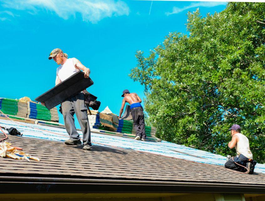 Team installing roof shingles